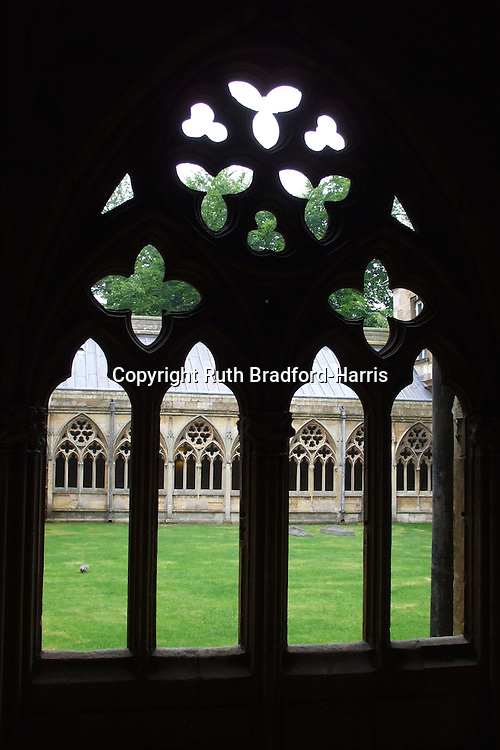 Sunlit cloisters at Lincoln Minster seen through the silhouette of a facing cloister window. <br /> <br /> Date taken: 06 June 2010.