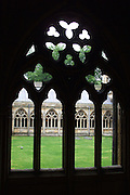 Sunlit cloisters at Lincoln Minster seen through the silhouette of a facing cloister window. <br />