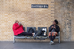 © Licensed to London News Pictures. 08/04/2020. London, UK. Two ladies eat and drink on a bench in from of the Harry Potter 9 3/4 platform sign inside an empty Kings Cross train station during the Coronavirus outbreak. The UK is currently on lockdown restrictions restricting travel to key workers only. Photo credit: Ray Tang/LNP