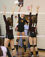 Solon's Jordan Smith (12) tries to hit the ball between the hands of Mount Vernon's Ali Platte (11) and Emma Cochrane (12) during the WaMaC Tournament semifinal game at Mount Vernon High School in Mount Vernon on Thursday October 11, 2012. Solon defeated Mount Vernon 26-24, 25-22.