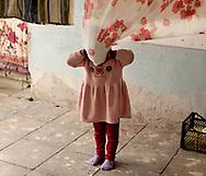 EN: A young girl hides behind hanging blankets at Tamuna's house. According to the few data available, Georgia has one the highest rates of female underage marriage among European countries.<br /> Kvemo Kartli region, Georgia, 2016. <br /> <br /> SP:Una niña juega con un mantel tendido al sol. Según los pocos datos disponibles Georgia es uno de los países europeo con los índices más altos de matrimonio infantil.