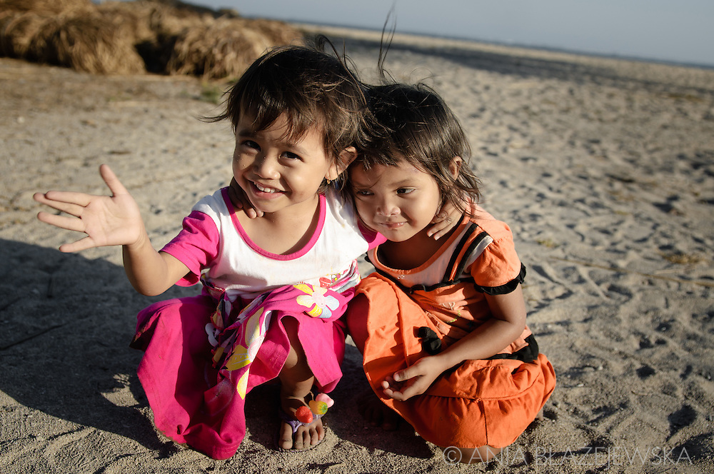 Two little happy girls on the beach in Kuta, Lombok.