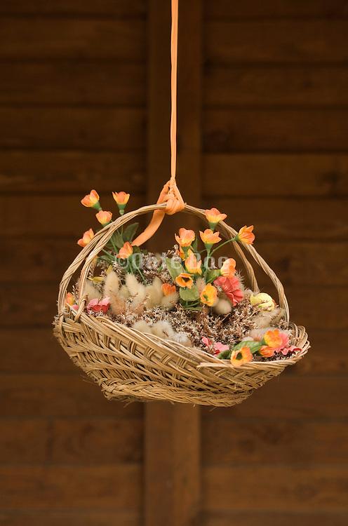 flower arrangement in straw basket hanging from a orange string