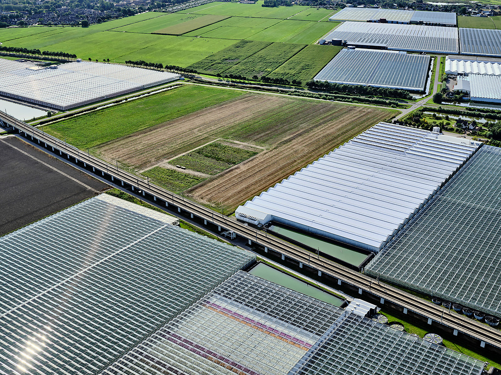 Nederland, Zuid-Holland, Bleiswijk, 14-09-2019; hogesnelheidslijn HSL doorsnijdt het kassengebied van Bleiswijk in de Overbuurtsche Polder.<br /> The rails of the HST between the greenhouses of the vegetables and fruit producers in the west of the Netherlands, skyline Rotterdam<br /> <br /> luchtfoto (toeslag op standard tarieven);<br /> aerial photo (additional fee required);<br /> copyright foto/photo Siebe Swart