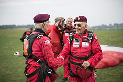 © Licensed to London News Pictures. 25/08/2016. <br /> <br /> Pictured: From left to right, Fred Glover and Ted Pieri, two D-Day veterans who are both 90 years old shake hands after having parachuted into Sarum Airfield, Wiltshire on Thursday 25th August 2016, 72 years after D-Day having earlier in the month parachuted into Merville Battery in France.<br /> <br /> <br /> Photo credit should read Max Bryan/LNP