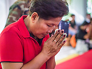 19 MAY 2013 - BANGKOK, THAILAND:   A Red Shirt supporter participates in a memorial service in Wat Pathum Wanaram in central Bangkok for people killed by the Thai army during the Red Shirt protests in 2010. More than 85 people, most of them civilians, were killed during the Thai army crackdown against the Red Shirt protesters in April and May 2010. The Red Shirts were protesting against the government of Abhisit Vejjajiva, a member of the opposition who became Prime Minister after Thai courts ruled the Red Shirt supported government was unconstitutional. The protests rocked Bangkok from March 2010 until May 19, 2010 when Thai troops swept through the protest areas arresting hundreds.  PHOTO BY JACK KURTZ