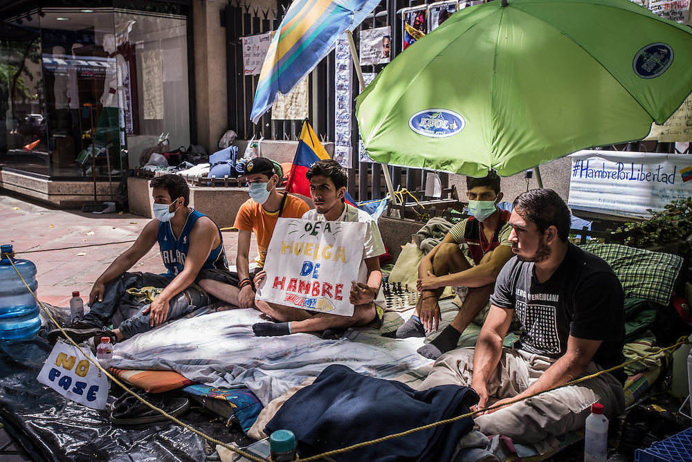 "CARACAS, VENEZUELA - MAY 20, 2016: University students have been holding a hunger strike in protest outside of the Caracas offices of the Organization of American States since May 11, 2016. The students say they will maintain their hunger strike until the OAS activates the Inter-American Democratic Charter and intervenes to restore judicial independence and the protection of basic human rights. They are also asking the OAS to help in the release of dozens of political prisoners, many who are students that were arrested during anti-government street protests. Tensions came to a head last week when President Maduro went on television to criticize the OAS, another longtime ally of the socialists, which is now criticizing Venezuela's handling of the economic and political crises. Mr. Maduro took aim at Luis Almagro, its secretary-general, calling him a ""longtime traitor"" and implying he was a spy.  Mr. Almagro responded with an open letter blasting the government. ""I am not a CIA agent,"" the letter said. ""You betray your people and your supposed ideology with your tirades.""  PHOTO: Meridith Kohut for The New York Times"