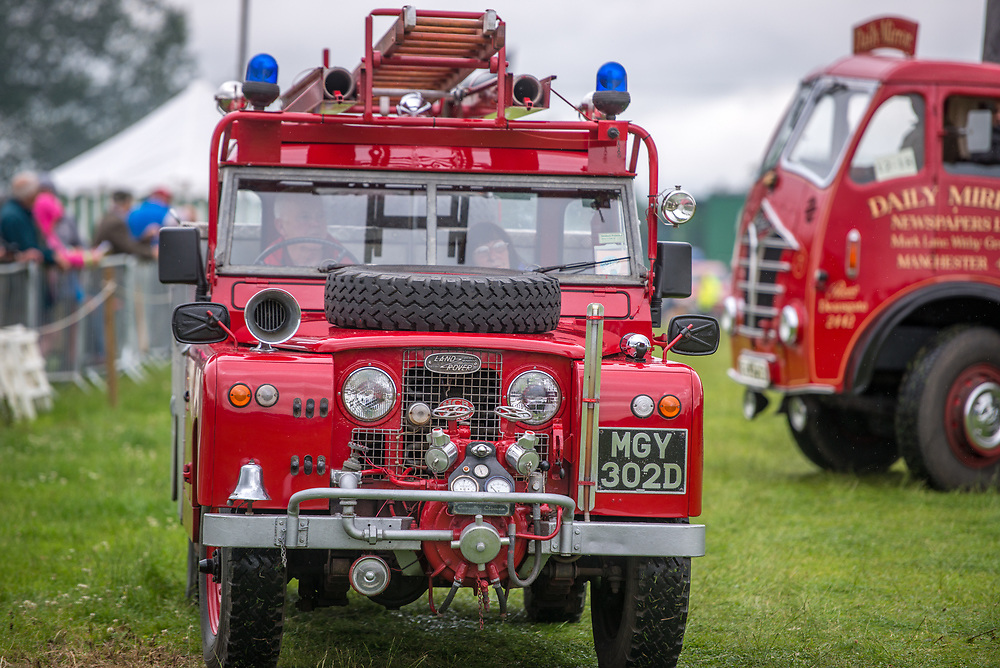 Front view of vintage Land Rover fire brigade vehicle being driven by a mature couple, Masham, North Yorkshire, UK