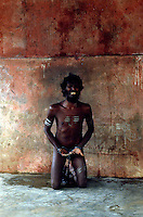 Tamil Nadu, INDIA. March1994..A man who has his hands and feet in chains, is kneeling, lamenting..This is the fate awaiting those, who the locals believe are possessed by evil spirits.