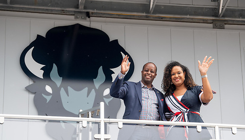 President Wayne A. I. Frederick and First Lady Simone Frederick smiling and waving in front of a Howard University bison logo.