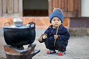 A Young Child is sitting alone beside a stove, holding chop sticks and a clam in his hand.