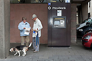 Europe, Germany, Cologne, older couple with dog in front of a cashpoint of the Pax-Bank. <br /> Europa, Deutschland, Koeln, aelteres Paar mit Hund vor einem Geldautomaten der Pax-Bank.