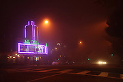 Foggy night time view of Los Angeles street showing  theatre marquee and distant car head lights