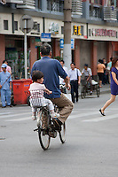 man with child on back of bike cycles through Shanghai China