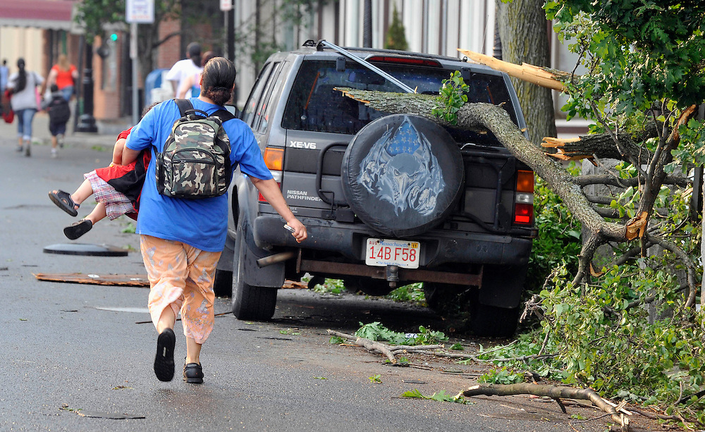 A woman runs with her child to safety after another report of a possible tornado in Springfield, Mass., Wednesday, June 1, 2011. An apparent tornado struck downtown Springfield, one of Massachusetts' largest cities, scattering debris, toppling trees, and frightening workers and residents. (AP Photo/Jessica Hill)