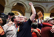 John Stumme, left, kisses his husband Kyle Hanson in the state capitol rotunda immediately after the news that the Minnesota Senate passed a bill making Minnesota the 12th state in the country allow gay marriage May 13, 2013.