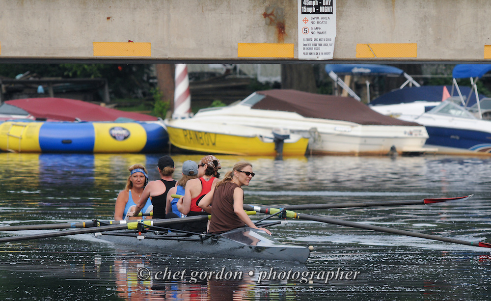 A team of four women and their coxswain pass under a roadway bridge during their morning row in Greenwood Lake, NY on Tuesday, July 9, 2013.  © Chet Gordon/THE IMAGE WORKS