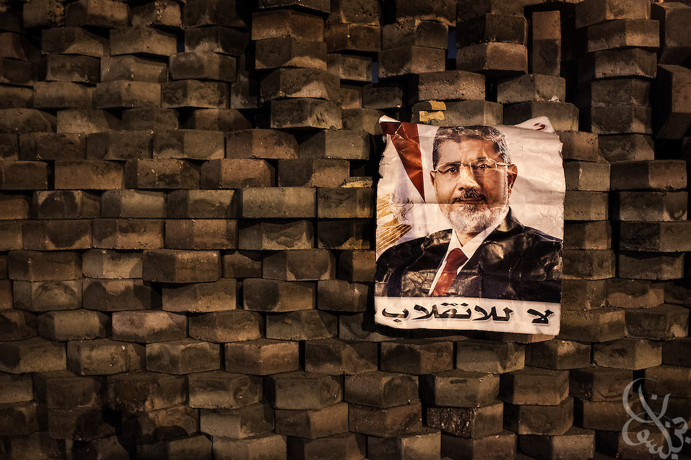 A poster image of deposed Egyptian president Mohamed Morsi adorns a recently constructed brick wall on the edges of continuing large scale demonstration and sit-in at the Rabaah al-Adawia square in the Nasr City district of Cairo Friday July 27, 2013.  Clashes nearby in the early hours of the day killed at least 65 pro-Morsi demonstrators and wounded thousands.