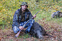 Young Romanian hunter posing with his first Wild boar (Sus scrofa) that he shot during a driving hunt in the forest area outside the village of Mehadia, Caras Severin, Romania.