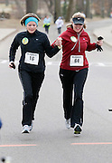 Rondel Spires, left, and Penny Newland cross the finish of the 5K Frosbite Run held at Ohio University Saturday, February 21, 2009 hand in hand.  Both runners were the race to show support for their friend,  Jaime Ridenour who had suffered a stroke recently.