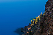 A rocky outcropping meets the pristine azure waters of Crater Lake, the deepest lake in the United States.