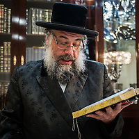 London, UK - 13 April 2014: Rabbi Osher Schapiro of the Jewish Community of Stamford Hill recites blessings after having searched for chametz (leavened bread products) in his house on the night before Passover.
