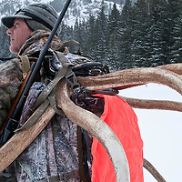 Hunter in the field, close up packing huge trophy antlers and riffle