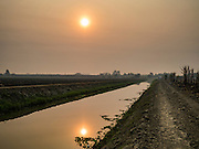 02 FEBRUARY 2016 - NONG LAN, KANCHANABURI, THAILAND: An irrigation canal that waters sugar cane fields in Kanchanaburi, Thailand. Thai sugar cane yields are expected to drop by about two percent for the 2015/2016 harvest because of below normal rainfall. The size of the crop is expected to increase slightly though because farmers planted more sugar cane acreage this year. Thailand is the second leading exporter of sugar in the world. Thai sugar growers are hoping a good crop would make up for shortages in global markets caused by lower harvests in Brazil and Australia, where sugar yields have been stunted by drought. Because of the drought in Thailand, sugar exports are expected to drop by up to 20 percent, contributing to a global sugar shortage. The drought is is also hurting the quality of Thai sugar, because sugarcane grown in drought is less sweet than normal so mills need to process more cane to make the same amount of sugar. Thai sugar farmers have lost 20 percent to 30 percent of their output this year because of the drought.          PHOTO BY JACK KURTZ