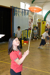 Young girl practising with spinning top in school sports hall,
