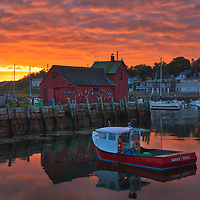 New England photo of the famous red fishing shack Motif #1 in Rockport, Massachusetts on Cape Ann. The photograph captures the local fishing boats with the iconic landmark and a stunningly beautiful sunrise sky. The historic landmark is known throughout New England as Motif #1, so called because it is the most often painted building in America.<br />