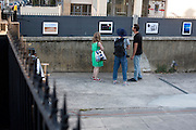 Looking at an photo exhibition in courtyard, Arles July5, 2016. © Carlo Cerchioli