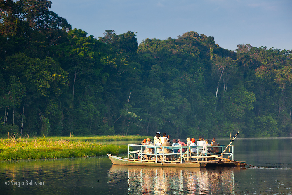 Specialized natural history bi-lingual guides take tourists to view wildlife on an oxbow lake next to the Tambopata River in Tambopata NP in the Peruvian Amazon.