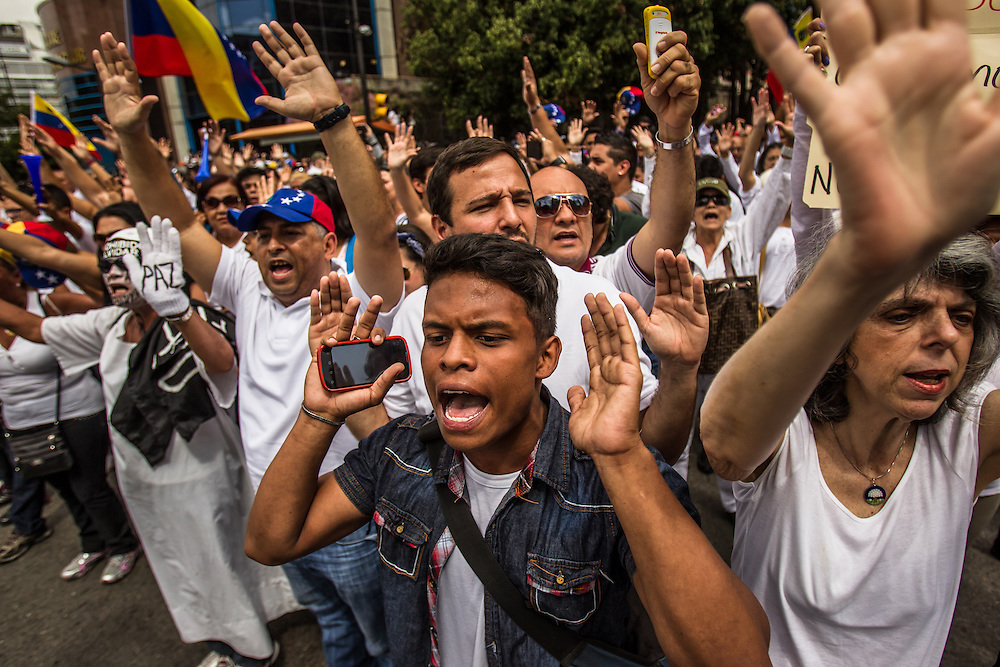 CARACAS, VENEZUELA - FEBRUARY 18, 2014:  Lopez supporters chant anti-government slogans. Thousands of people took to the streets today to support opposition leader Leopoldo López as he surrendered to Police during a peaceful march in Caracas.  The government has said López is responsible for inciting recent street protests, that have killed three people. CREDIT: Meridith Kohut for Bloomberg News