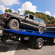 A flatbed truck drives down south main street towing a water damage late model SUV Saturday, Sept. 10, 2011 in Port Deposit, Md as flooding from the Susquehanna River continues. (AP Photo/Saquan Stimpson)