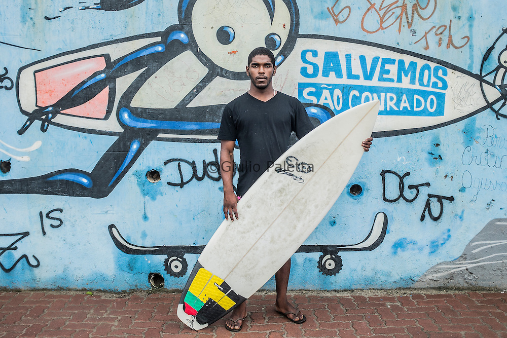 "Carlos ""Mister M"", 22, surfer. Two years ago he co-founded Rocinha Surfers Association, which survives with donations, including from pro surfers such as Julian Wilson. Working as a surf teacher fulfils his dream of living for surfing. Also a Rua 2 resident, he was abandoned by his alcoholic parents when he was born, lived with his also drunken maternal grandmother until he was one and a half years old, and then, when after almost dying from pneumonia, he went to live with her paternal grandma. He knows how important the sport is to keep kids away from drug dealers. His project is also focused on the importance of letting children aware of pollution and educates them to not throw trash away in Rocinha alleys. He believes in the power kids have to even change grownups' minds about environmental issues, showing how it could impact deeply on their wave. After a few years away from school, he's now back, about to finish junior high. After high school, he wants to study Sports Marketing at college. Bringing the World Tour event to São Conrado is his next goal."