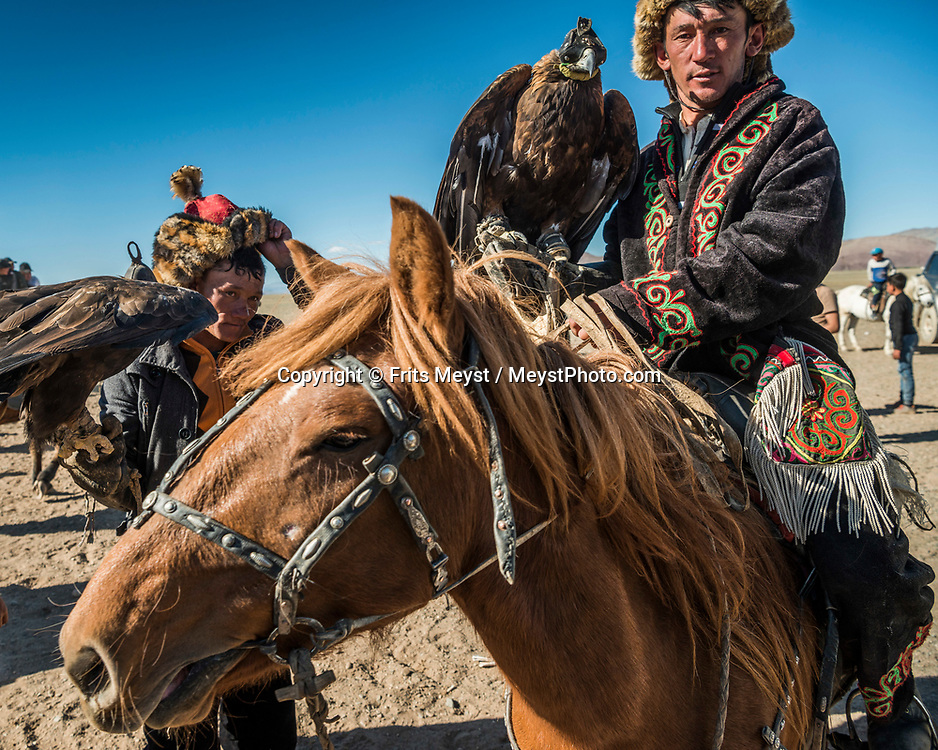 Ulgii, Altai Mountains, Mongolia, September 2017.  Winning eagle hunters collect their awards and celebrate after the games. Ethnic Kazakh horsemen from all over the Altai mountains gather in a dusty valley for the annual Altai Golden Eagle Festival. At this two day event, they compete in centuries old Eagle hunting skills, marksmanship and horsemanship. Nowadays, small groups of tourists attend the festival, but in no way is this a tourism event.  Photo by Frits Meyst / MeystPhoto.com