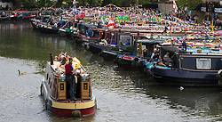 Little Venice, London, April 30th 2017. Narrowboaters from all over the uK gather for the annual Canalway Cavalcade, held on the May Day Bank holiday weekend, organised by the Inland Waterways Association, where boaters get the chance to display their immaculately prepared and brightly painted craft as well as compete in various manoeuvring tests. PICTURED: A narrowboat makes its way past the moored boats in Paddington Basin.<br /> Credit: ©Paul Davey<br /> To licence contact: <br /> Mobile: +44 (0) 7966 016 296<br /> Email: paul@pauldaveycreative.co.uk<br /> Twitter: @pauldaveycreate