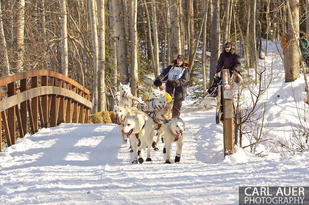 March 7th, 2009:  Anchorage, Alaska - Jim Lanier of Chugiak, Alaska brings his team across a foot bridge near Behm Lake during the 2009 Ceremonial Start to the Iditarod Sled Dog Race.