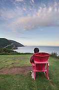 Tourist taking in the view from a red adirondack chair at viewpoint, Cape Breton Highlands National Park, Cape Breton Island Nova Scotia