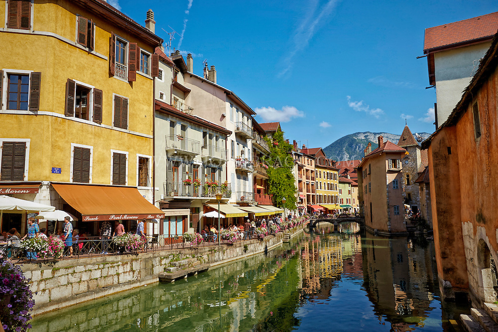 View of The French Alps, and colorful buildings seen along the Thiou Canal, Old Town Annecy, France.