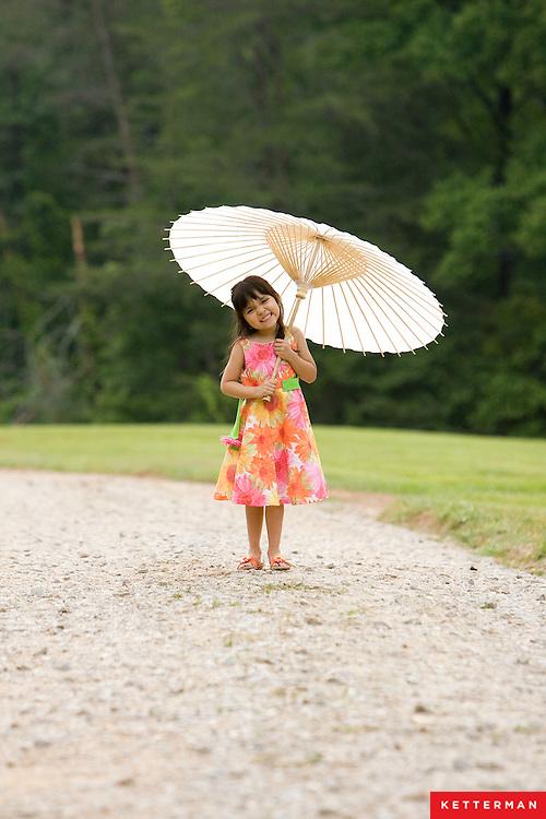 A cute little girl walks down a path with her umbrella.