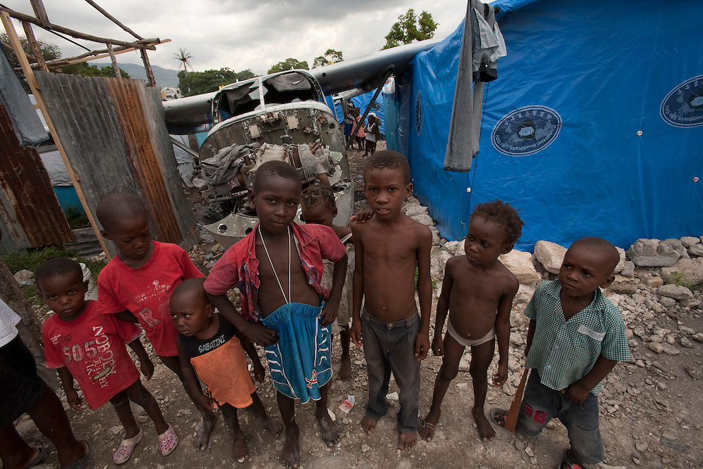 Boys in the makeshift refugee camp, La Piste, in Port-au-Prince, Haiti on July 15, 2010. <br /> <br /> La Piste (French for &quot;runway&quot;)is a settlement sprawled across the site of a disused airport and now home to an estimated 20,000 earthquake survivors living in makeshift structures.<br /> Six month after a catastrophic earthquake measuring 7.3 on the Richter scale hit Haiti on January 13, 2010, killing an estimated 230,000 people, injuring an estimated 300,000 and making homeless an estimated 1,000,000.