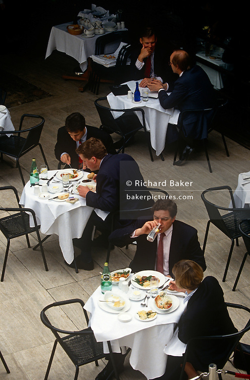An aerial view of city of London businessmen (and one lady) using the opportunity for business lunches at three tables outside in the city complex known as Broadgate Circle, an eighties development of offices and trading institutions. The three tables each have crisp white table cloths, cutlery and plates and green bottles of Perrier mineral water, rather than alcohol.