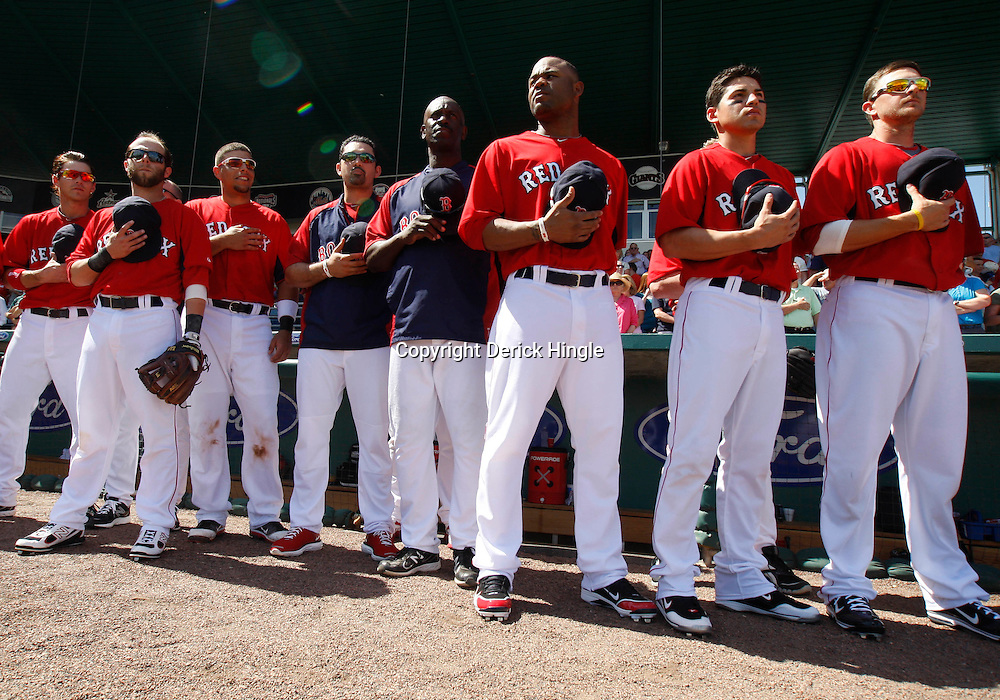 February 28, 2011; Fort Myers, FL, USA;Boston Red Sox left fielder Carl Crawford (center) and teammates stand for the national anthem before a spring training exhibition game against the Minnesota Twins at City of Palms Park.  Mandatory Credit: Derick E. Hingle