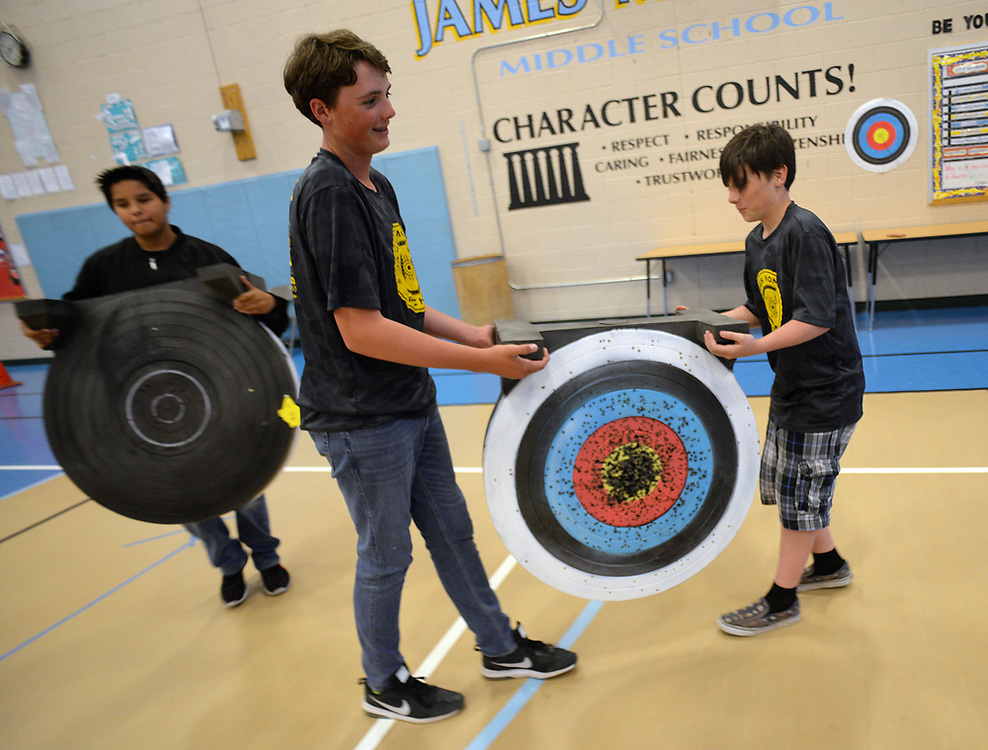 apl050817a/SPORTS/pierre-louis/JOURNAL 050817<br /> James Monroe Middle School Archery teammates from left Janae Sisneros,, 13, Walker Schultz,, 12, and Asher Arbuckle,,11,  move  targets before practice . The team recently won a state championship and  will compete in Kentucky May 11 -14  .Photographed on Monday May 8 2017. .Adolphe Pierre-Louis/JOURNAL