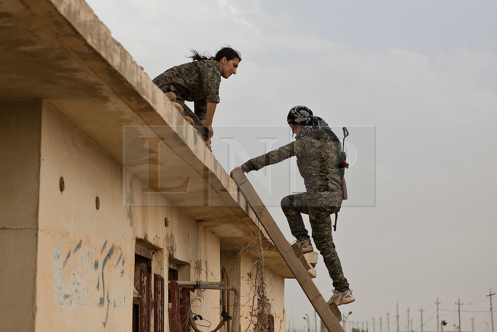 © Licensed to London News Pictures. 28/09/2014. Rabia, Iraq. Two female fighters belonging to the Syrian-Kurdish YPJ are seen on a roof top position in the Iraqi border town of Rabia.<br /> <br /> Facing each other across the Iraq-Syria border, the towns of Al-Yarubiyah, Syria, and Rabia, Iraq, were taken by Islamic State insurgents in August 2014. Since then The town of Al-Yarubiyah and parts of Rabia have been re-taken by fighters from the Syrian Kurdish YPG. At present the situation in the towns is static, but with large exchanges of sniper and heavy machine gun fire as well as mortars and rocket propelled grenades, recently occasional close quarter fighting has taken place as either side tests the defences of the other. Photo credit: Matt Cetti-Roberts/LNP