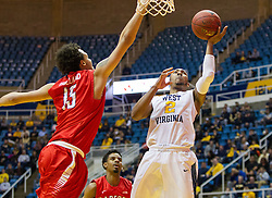Dec 20, 2016; Morgantown, WV, USA; West Virginia Mountaineers guard Jevon Carter (2) shoots under the basket over Radford Highlanders forward Devonnte Holland (15) during the second half at WVU Coliseum. Mandatory Credit: Ben Queen-USA TODAY Sports