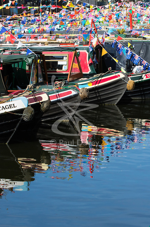 Little Venice, London, May 1 2016. Bright sunshine greets narrow boaters at the Inland Waterways Association's annual Canalway Cavalcade, a get-together of narrow boaters from all over the UK, on the May Day bank holiday. PICTURED: Colourful bunting, a blue sky and ornately painted narrowboats create colourful reflections. ©Paul Davey<br /> FOR LICENCING CONTACT: Paul Davey +44 (0) 7966 016 296 paul@pauldaveycreative.co.uk