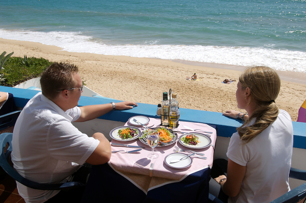 A young couple eating on the balcony overlooking the beach on the Algarve, Portugal