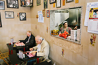 NAPLES, ITALY - APRIL 10th 2018: Customers have lunch while owner Marianna Sorrentino is seen in the kitchen of the Trattoria Malinconico, a popular restaurant in the Vomero district in Naples, Italy, on April 10th 2018.<br /> <br /> Trattoria Malinconico was opened in 1953 by current owner Marianna Sorrentino's parents-in-law. At first it was only a bulk wine cellar, but then he began making a few cooked dishes – small plates that were popular with locals, which eventually morphed into larger meals. Still today the trattoria is frequented the neighborhood's older residents, many of whom have been loyal regulars for years, as well as younger locals and workers, who often stop by for a glass of wine. The menu varies from day to day, and is typically based on traditional Neapolitan recipes. Though some dishes, like meatballs, sausages, and friarielli (rapini, a type of broccoli typical to Naples), are always available.<br />  <br /> <br /> Genovese sauce is a rich, onion-based pasta sauce from the region of Campania, Italy. Likely introduced to Naples from the northern Italian city of Genoa during the Renaissance, it has since become famous in Campania and forgotten elsewhere.<br /> Genovese sauce is prepared by sautéing either beef, veal or pork in a large number of onions, for at least two but as many as ten hours. Large, cylindrical pasta like rigatoni, ziti or candele are favored because they can hold the rich sauce.